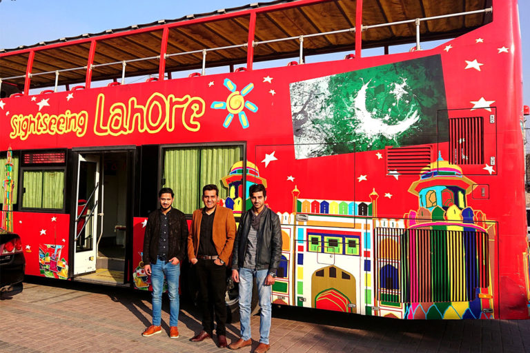 3 members of Moshpit team standing in front of Lahore sightseeing bus